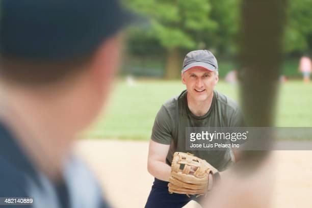 caucasian men playing baseball on field - bate fotografías e imágenes de stock