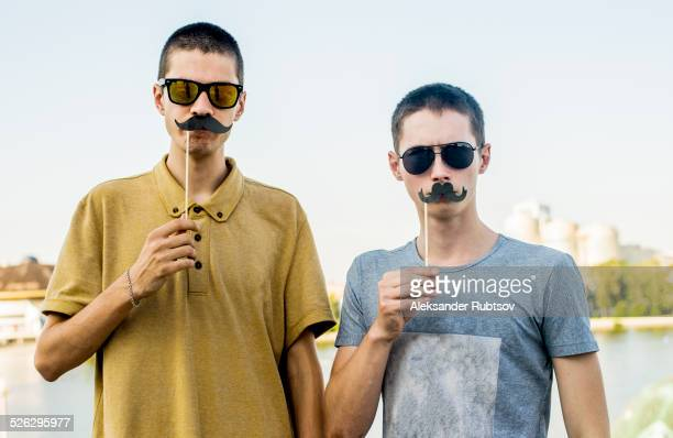 Caucasian men playing with fake mustaches in city