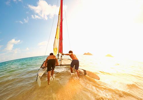Caucasian men pushing sailboat into ocean from beach - gettyimageskorea