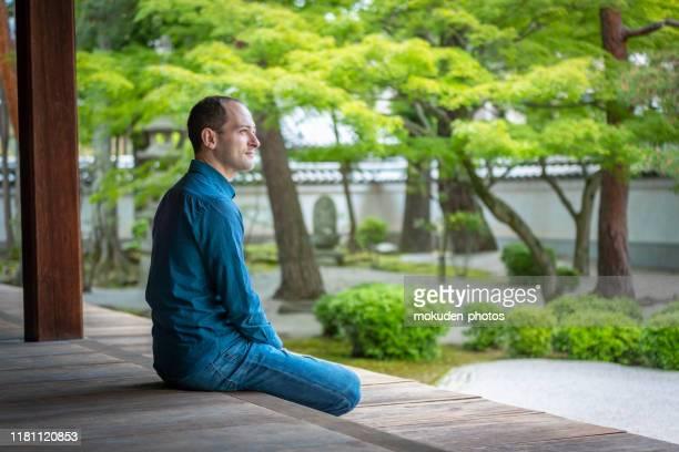 寺院の庭でリラックスする白人男性 - 整形式庭園 ストックフォトと画像