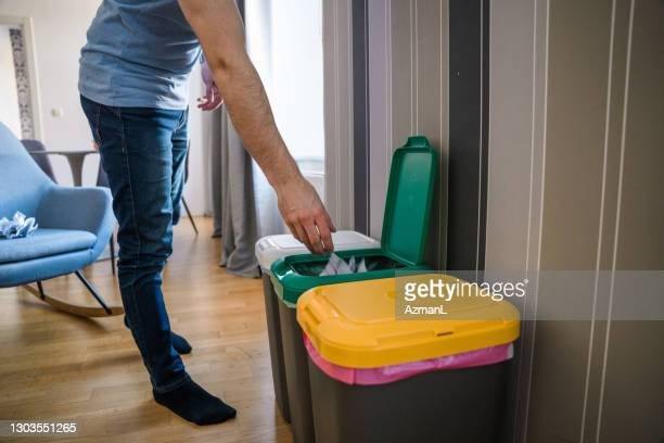 caucasian mid adult man recycling paper and putting into a garbage bin - absence stock pictures, royalty-free photos & images