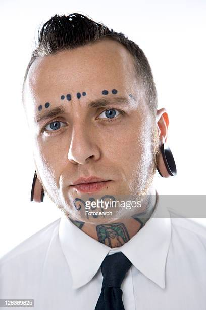 Caucasian mid-adult man with tattoos and piercings wearing necktie.