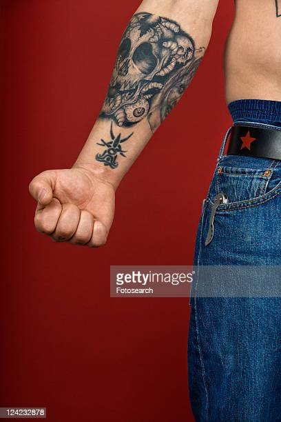 Caucasian mid-adult man's arm with tattoo.