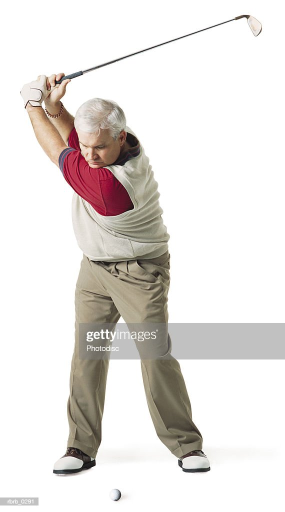 caucasian middle aged man wears red and tan swings golf club over his head preparing to hit the ball : Stockfoto