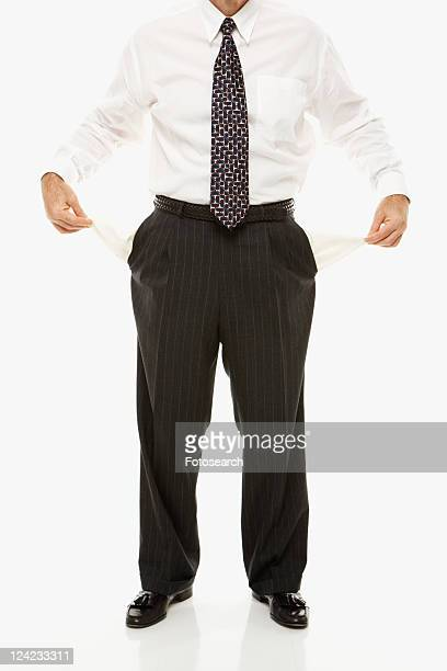 Caucasian middle-aged businessman pulling empty pockets out standing against white background.