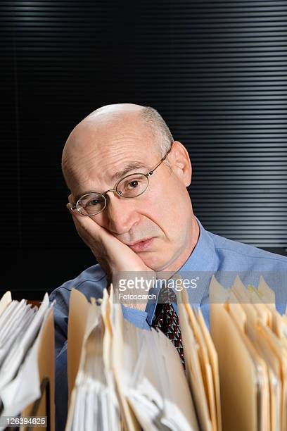 Caucasian middle-aged businessman with files leaning head on hand looking tired.