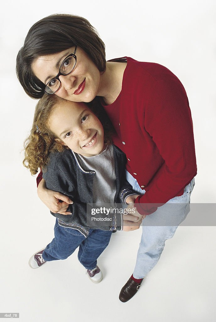 caucasian mom in glasses and red shirt holds smiling redhead daughter : Foto de stock
