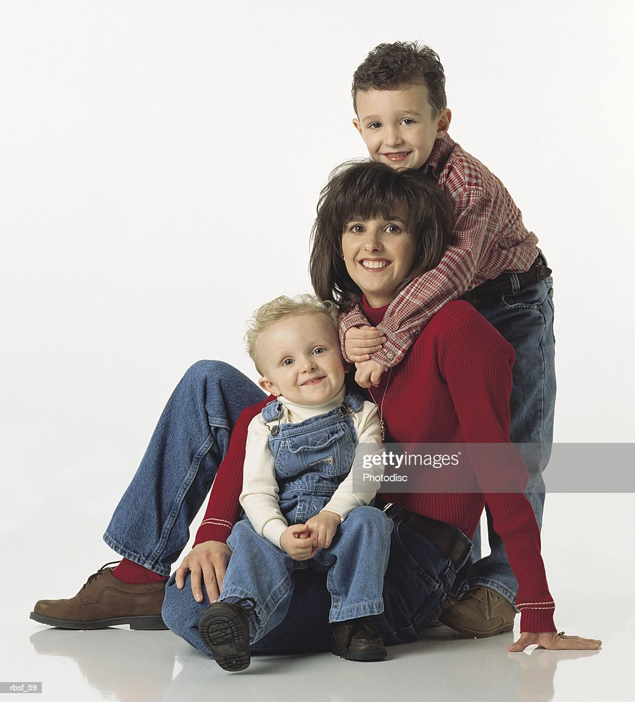 caucasian mom in red shirt sits with one child on her lap and one on her back : Foto de stock