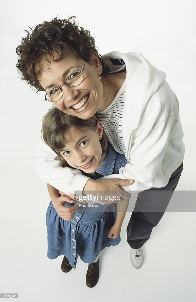caucasian mom/grandma with glasses has arm around her girl and leans over her smiling : Foto de stock