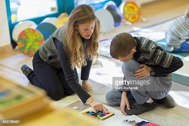 caucasian montessori teacher helping student in classroom - montessori education stock pictures, royalty-free photos & images