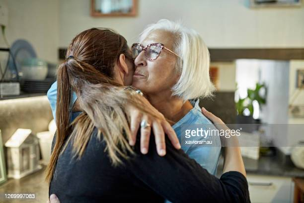 caucasian mother and adult daughter embracing - emotional support stock pictures, royalty-free photos & images