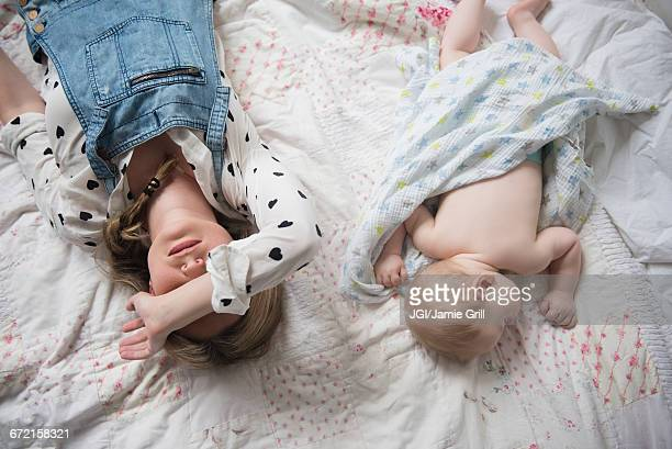 Caucasian mother and baby boy napping on bed