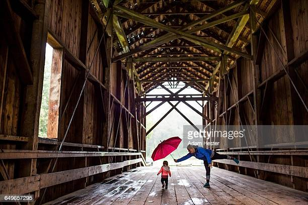 caucasian mother and baby daughter on covered bridge - covered bridge stock pictures, royalty-free photos & images