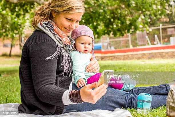 Caucasian mother and baby daughter using cell phone in park
