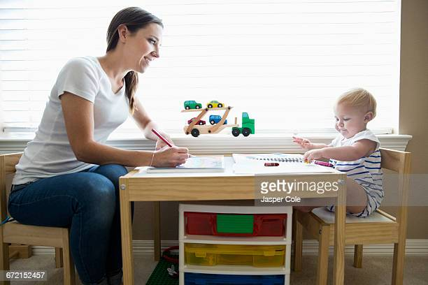 Caucasian mother and baby daughter using coloring books