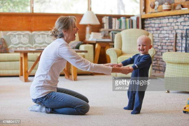 Caucasian mother and baby playing in living room