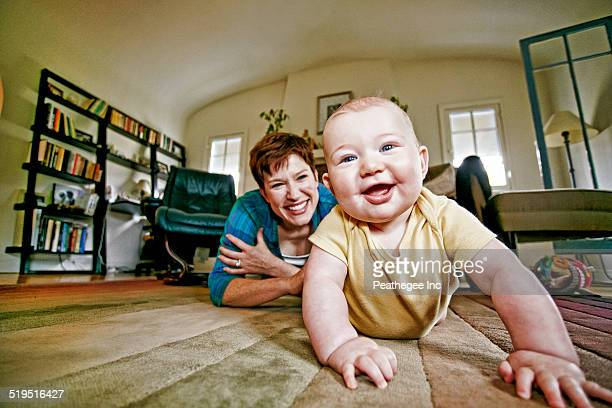 Caucasian mother and baby playing on living room floor