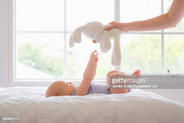 Caucasian mother and baby playing with stuffed animal in bedroom