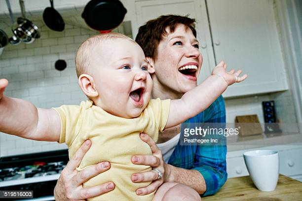Caucasian mother and baby relaxing in kitchen