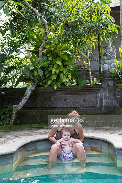 Caucasian mother and baby relaxing in swimming pool