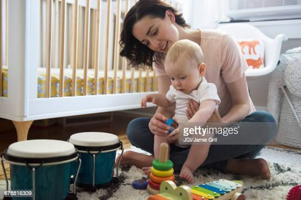 caucasian mother and baby son playing with toys on floor - mom sits on sons lap stock pictures, royalty-free photos & images