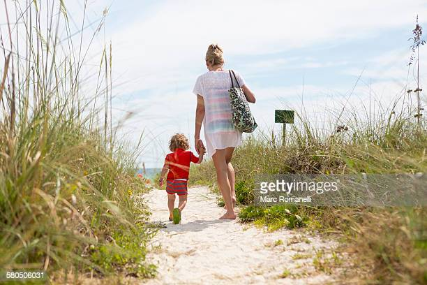 Caucasian mother and baby son walking on beach