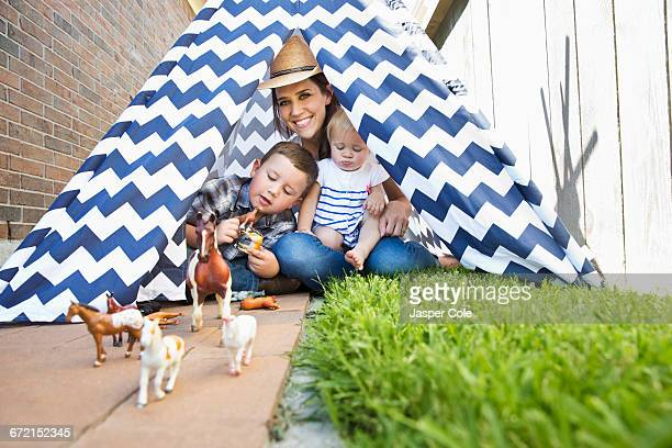 Caucasian mother and children in teepee playing with toy horses