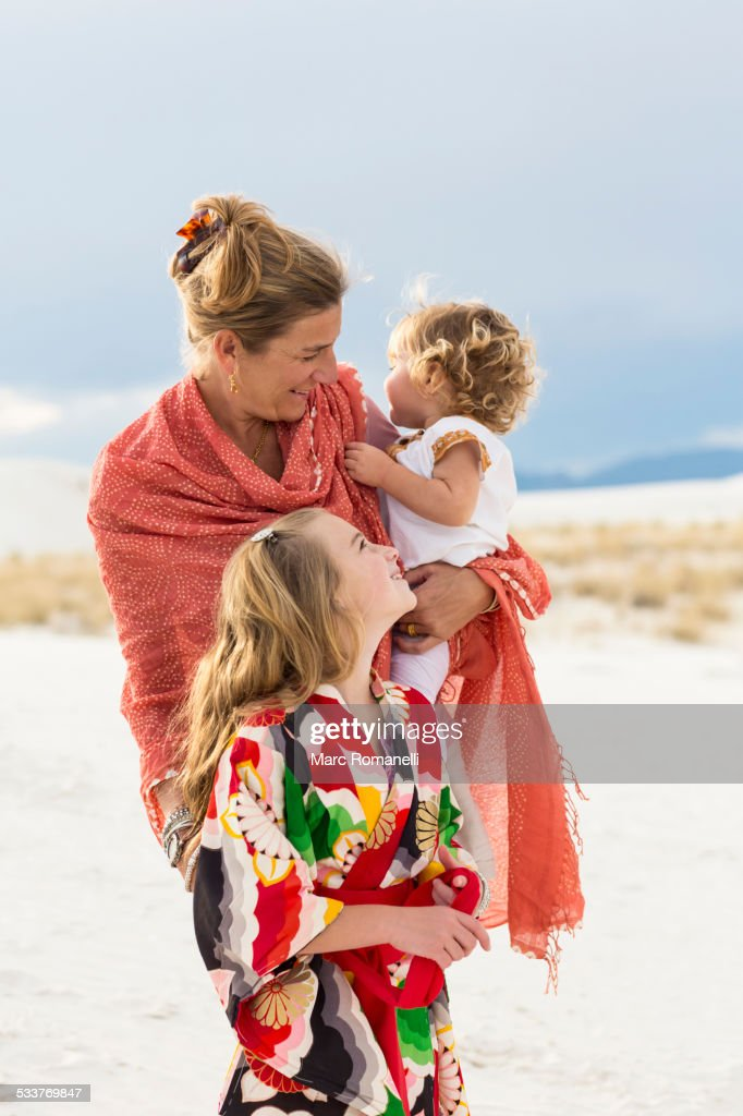 Caucasian mother and children laughing on sand dune : Foto stock