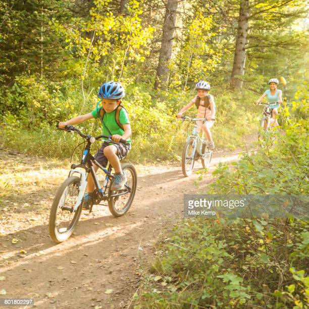 Caucasian mother and children riding mountain bikes