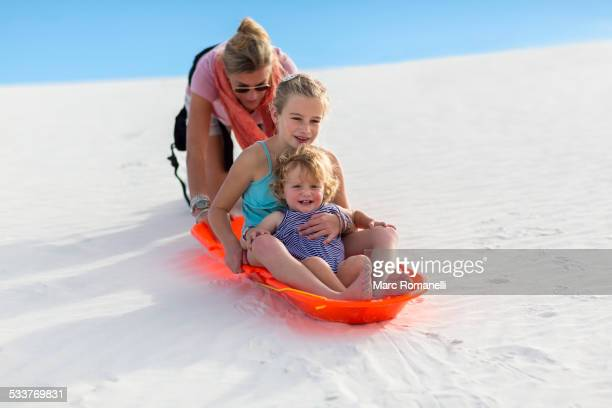 caucasian mother and children sledding on sand dune - tobogganing stock pictures, royalty-free photos & images