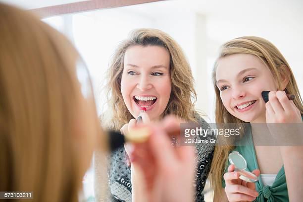Caucasian mother and daughter applying makeup in mirror