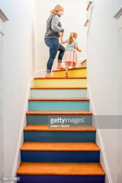 Caucasian mother and daughter climbing multicolor staircase