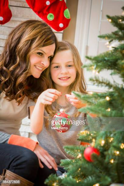 Caucasian mother and daughter decorating Christmas tree