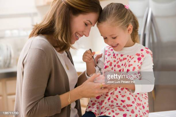 Caucasian mother and daughter eating ice cream