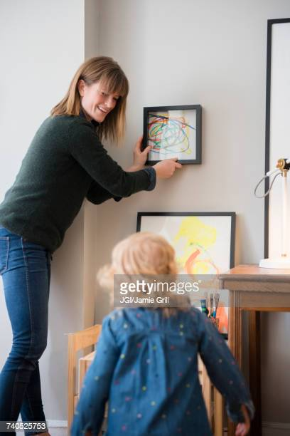 caucasian mother and daughter hanging her painting on wall - hanging stock photos and pictures