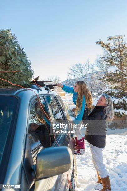 Caucasian mother and daughter hauling Christmas tree