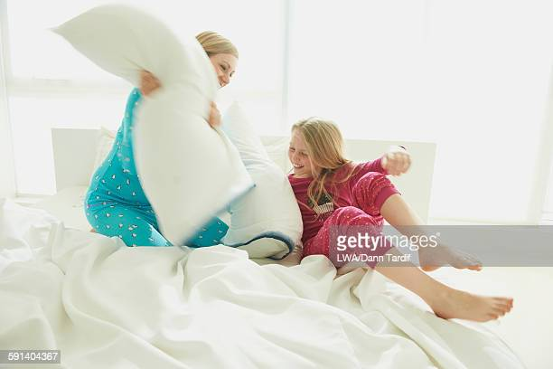 Caucasian mother and daughter having pillow fight on bed