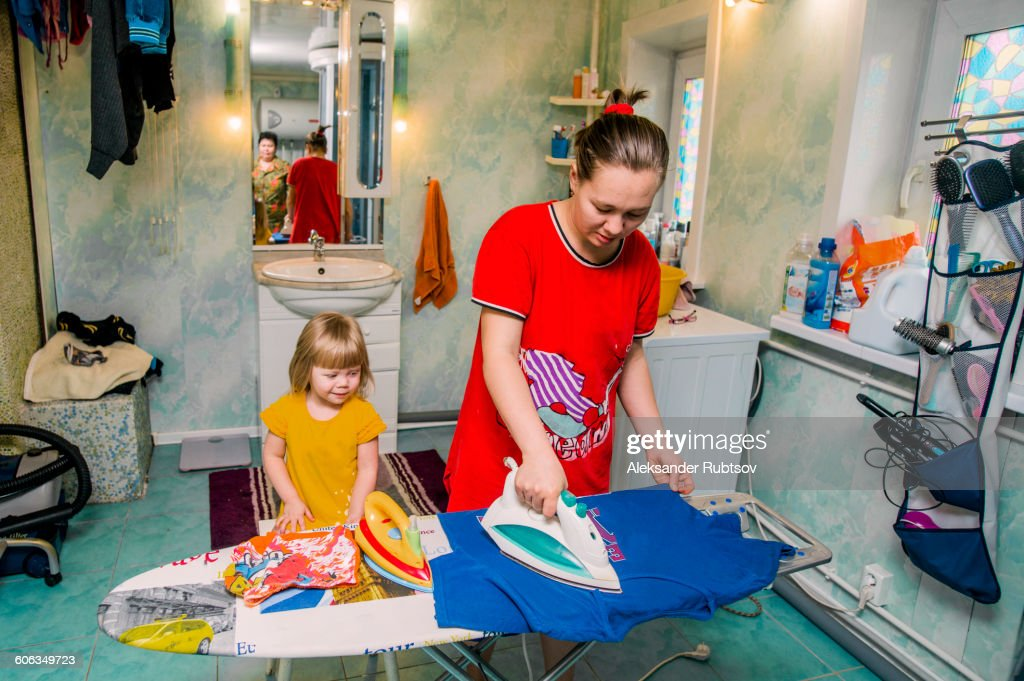 Caucasian mother and daughter ironing laundry
