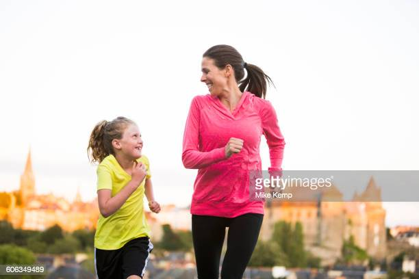 caucasian mother and daughter jogging outdoors - daily sport girls stock pictures, royalty-free photos & images