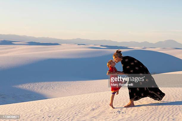 Caucasian mother and daughter kissing in desert