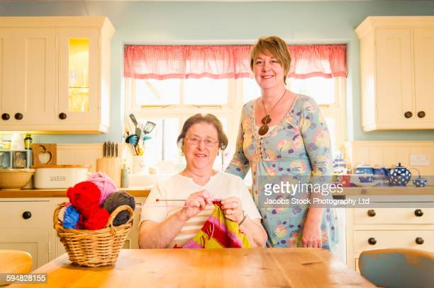 Caucasian mother and daughter knitting
