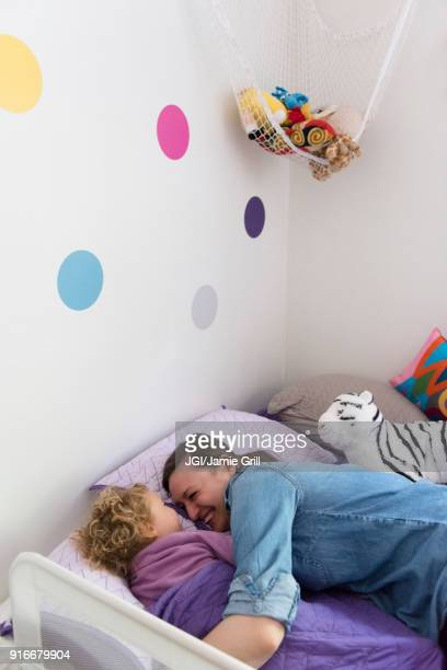 Caucasian mother and daughter laughing and cuddling in bed