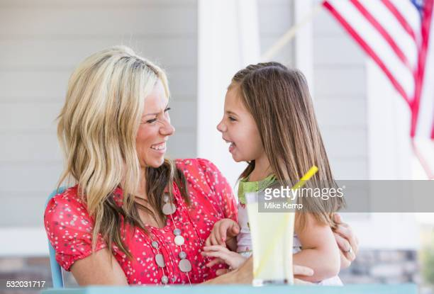 Caucasian mother and daughter laughing on porch
