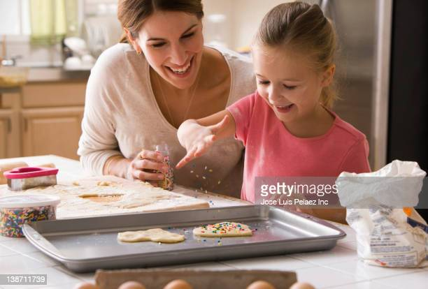 caucasian mother and daughter making valentine cookies - valentine's day holiday stock pictures, royalty-free photos & images