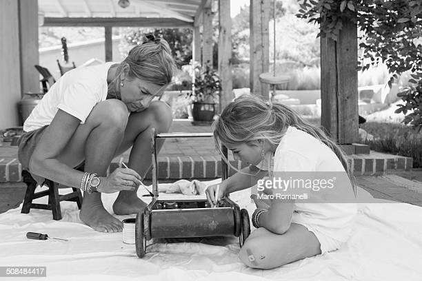 Caucasian mother and daughter painting toy on porch