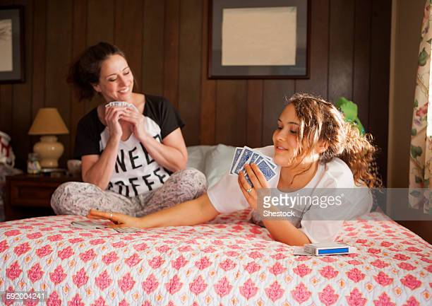 Caucasian mother and daughter playing cards in bedroom