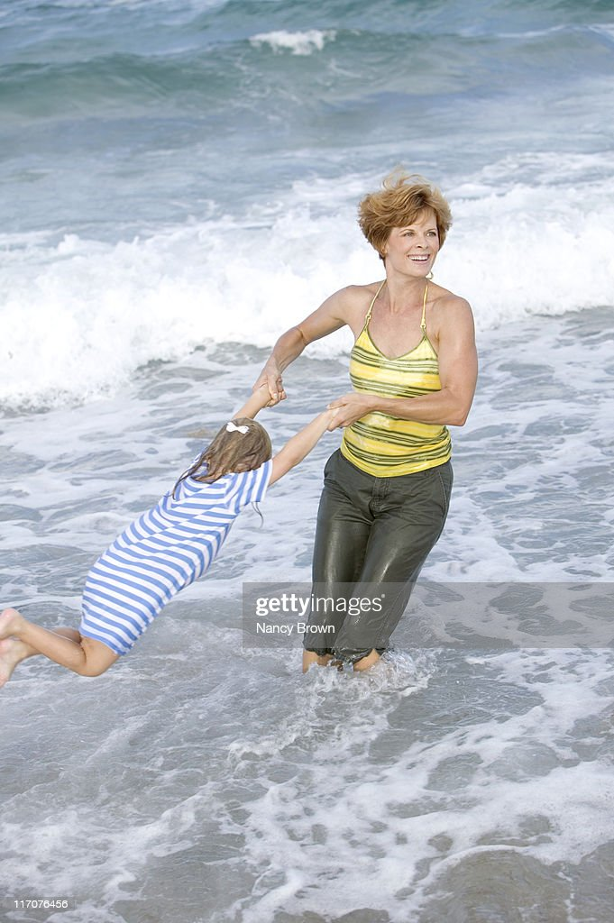 Caucasian Mother and daughter playing in ocean. : Stock Photo