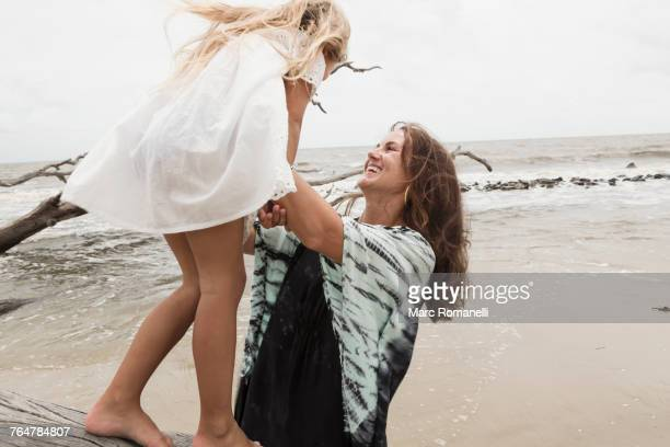 Caucasian mother and daughter playing on driftwood on beach