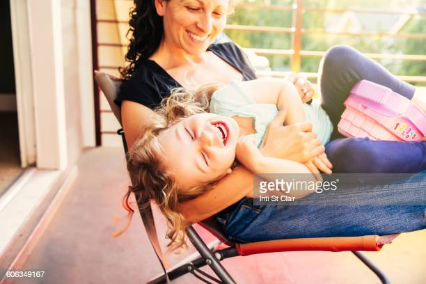 Caucasian mother and daughter playing on patio