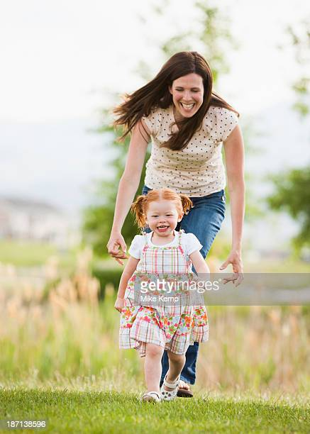 Caucasian mother and daughter playing outdoors